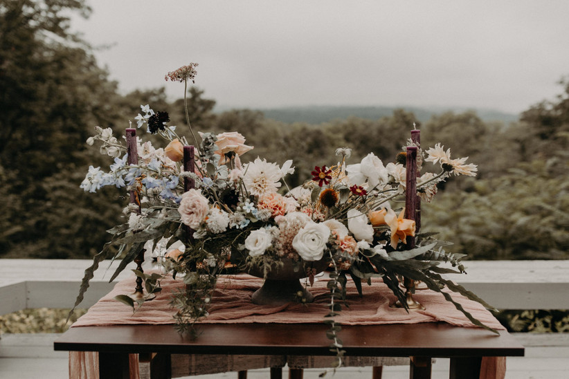 boho wedding centerpiece with white, blush, blue, and dark orange flowers on a table outdoors with tall burgundy candles on both sides
