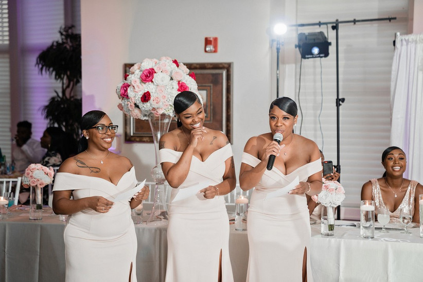 three bridesmaids stand up at the wedding reception to give a speech