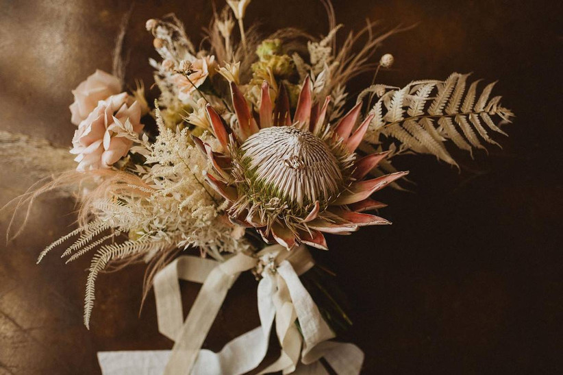 king protea bouquet with roses and ferns tied with silk ribbons