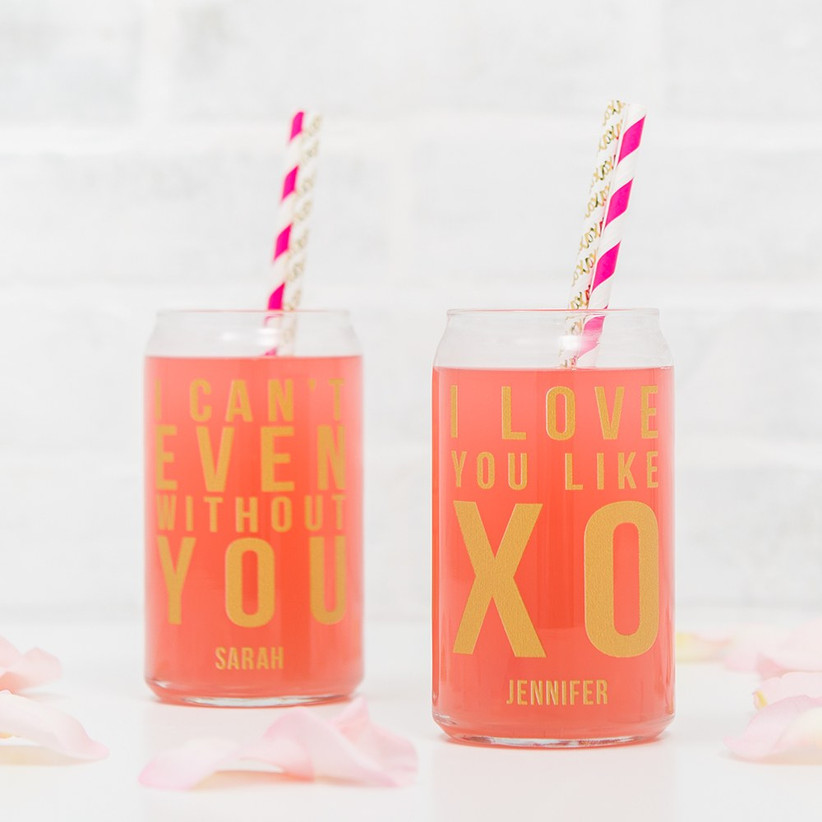 Two can-shaped cocktail glasses with colorful straws and fun slogans
