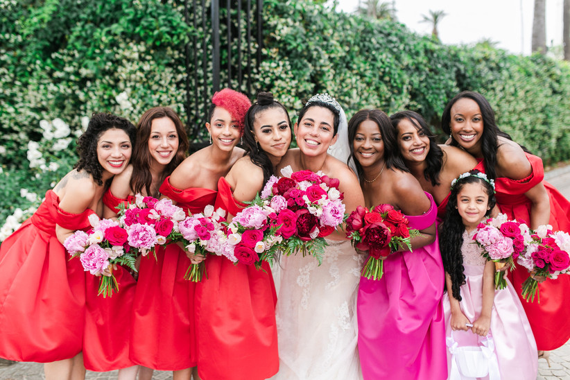 smiling bride poses with her bridesmaids and flower girl holding peony and rose bouquets