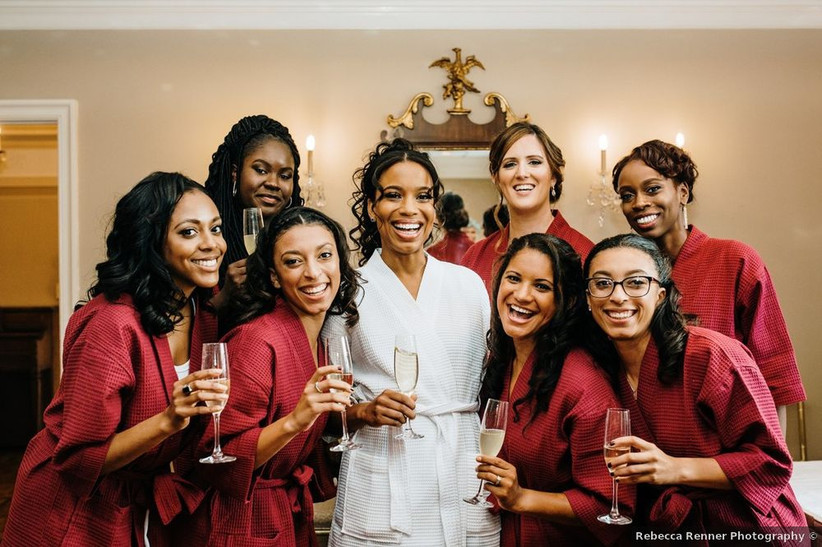 Black bride wears a white spa robe and is surrounded by her group of bridesmaids who are wearing burgundy robes. They are holding glasses of champagne in their hands