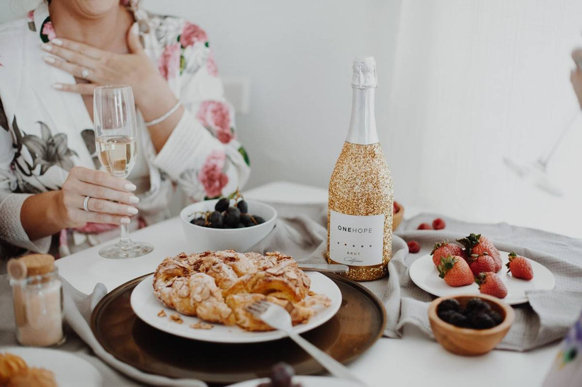 bride sits at brunch table with pastries, fresh berries and bottle of champagne with glitter label