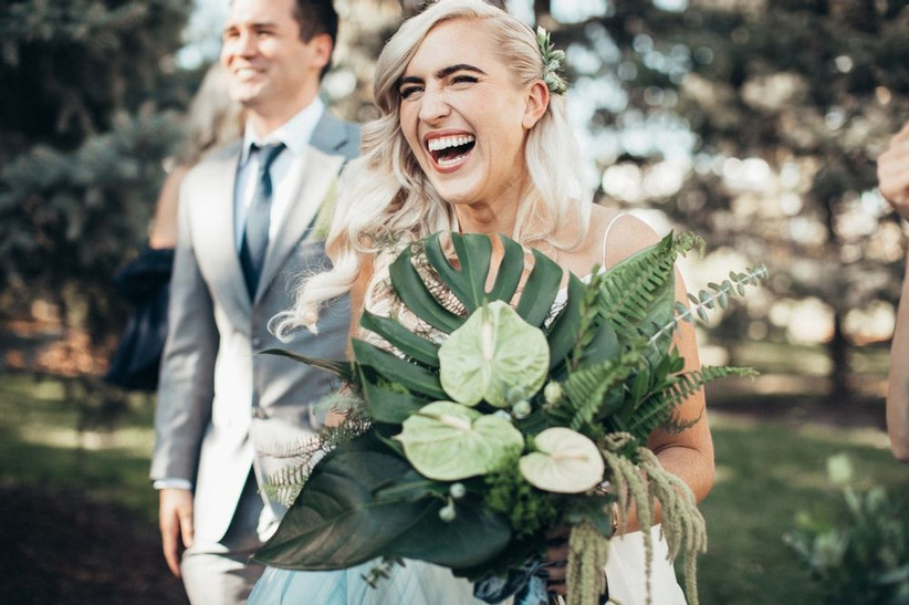 laughing bride holds tropical greenery wedding bouquet with monstera leaf, amaranthus, ferns, and anthurium