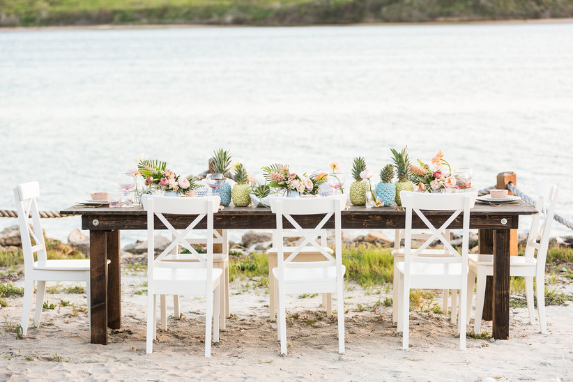 long banquet table next to lake with white wooden x-back chairs and painted blue and green pineapples in a line down the center of the table