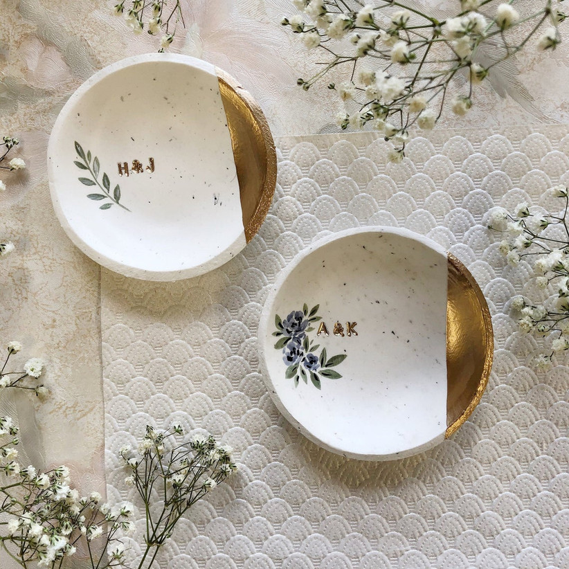 Two custom white and gold ring dishes with couple's initials