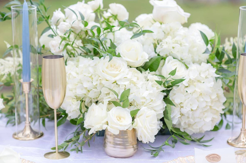 wedding centerpiece with white flowers roses and hydrangeas accented by light blue taper candles and gold champagne flutes