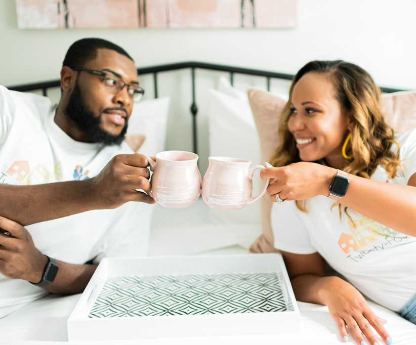 couple relaxing on bed with coffee mugs staycation at home