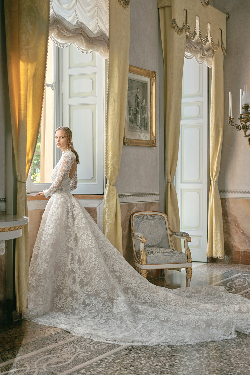 bride stands by the window in an opulent ballroom while wearing a lace ball gown with long train