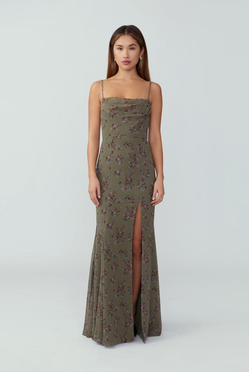 Model wearing minimalist sage green floral spaghetti strap dress with leg slit