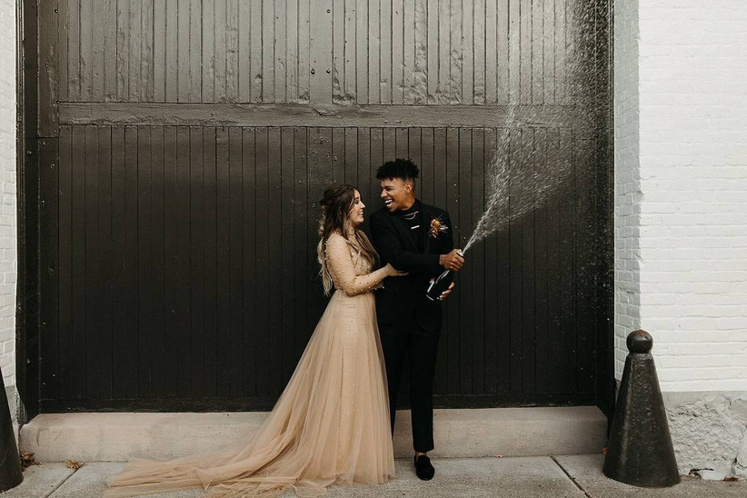 interracial couple pops champagne and smiles at each other after wedding ceremony