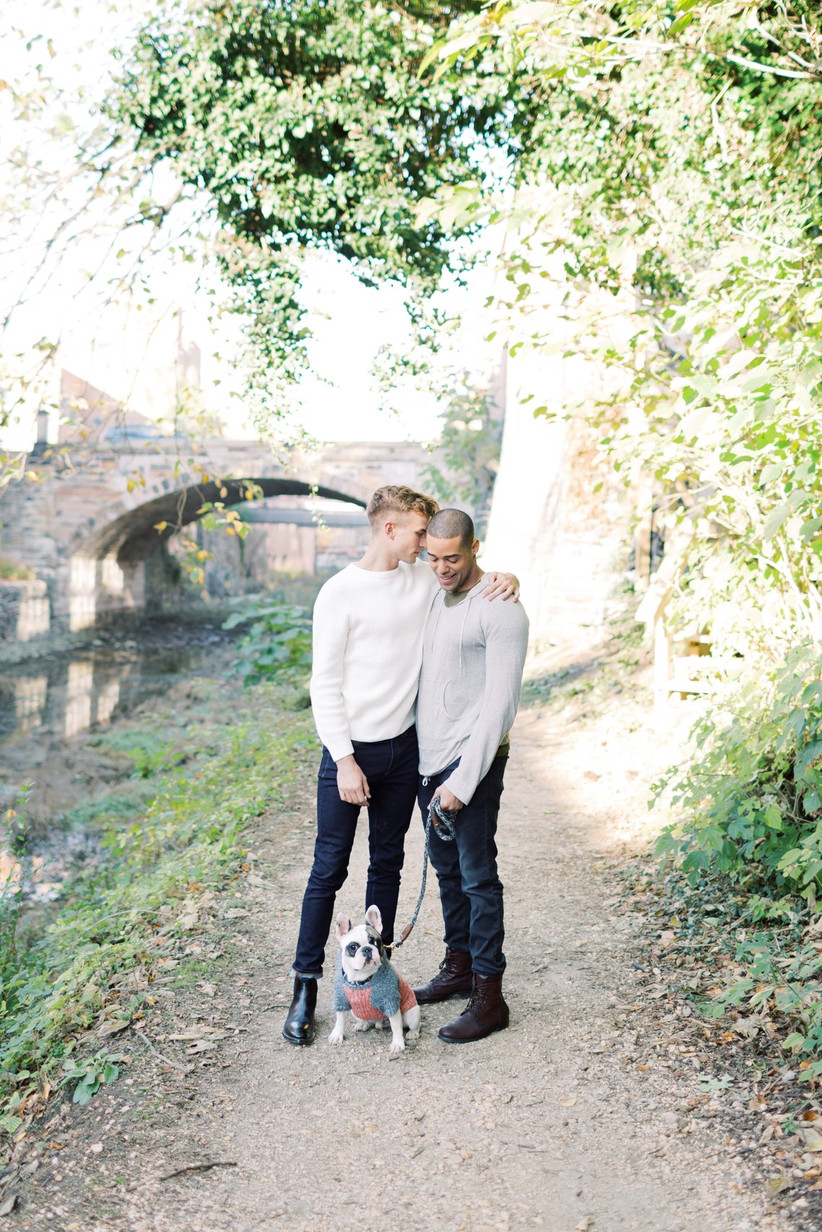 Same-sex couple standing outside at Georgetown Canal in Washington DC with French Bulldog