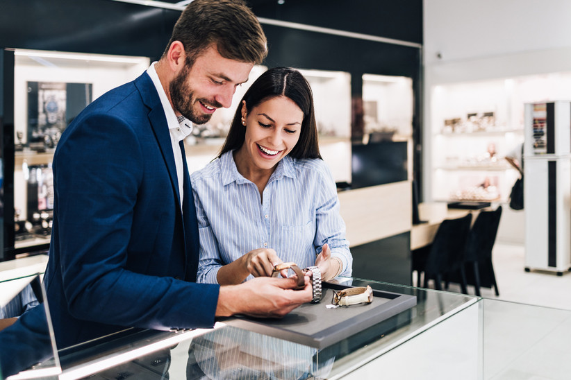 Happy couple smiling and looking at watches in a jewelry store