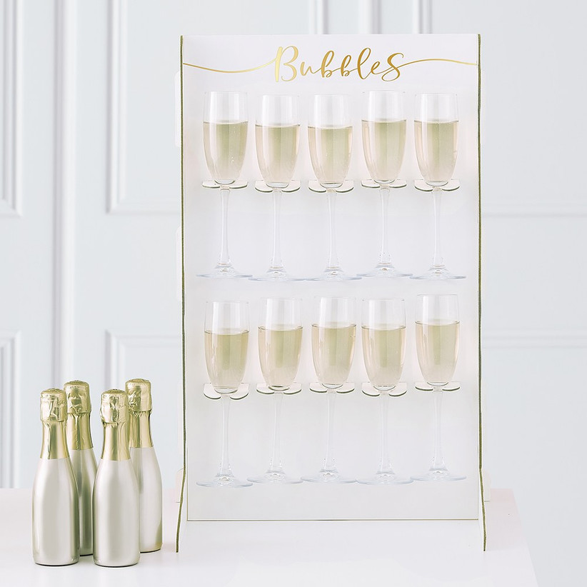 Champagne wall holding ten glasses of bubbly with Bubbles written in gold lettering at the top