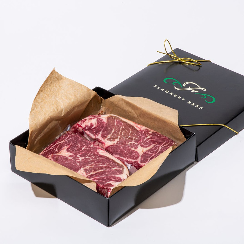 Flannery Beef black gift box with the lid off the reveal two juicy steaks