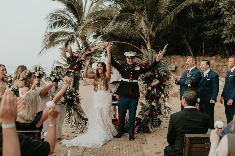 couple celebrates at outdoor wedding ceremony with palm trees in the background. the groom is wearing marine dress blues