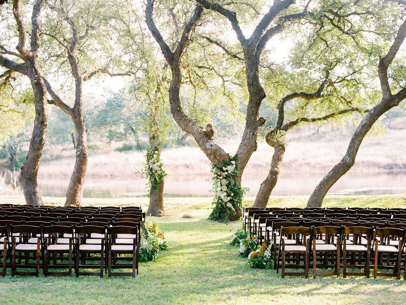 simple wedding ceremony backdrop with flowers decorating tree trunks