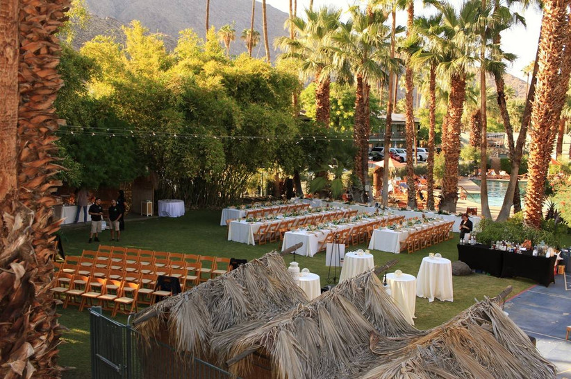 outdoor wedding ceremony and reception space surrounded by palm trees