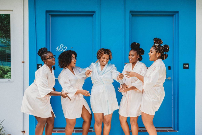 bride and bridesmaids wear matching white robes and dance