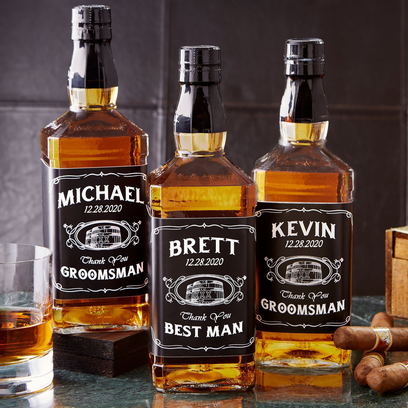 Whiskey bottles with personalized groomsman thank-you labels