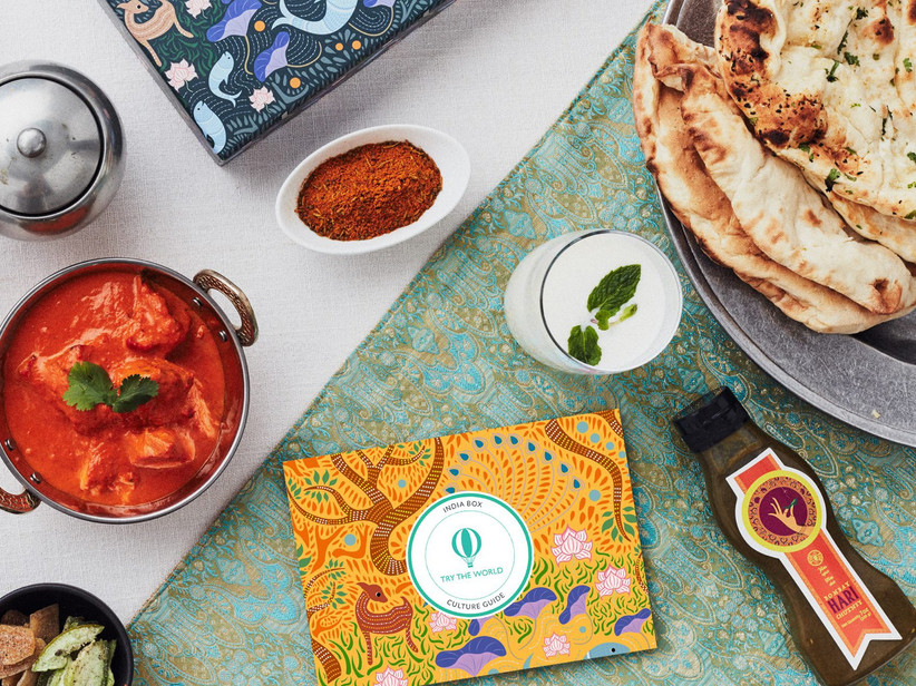 Try The World subscription box surrounded by a variety of food