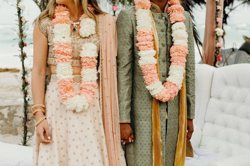 learn how to plan a wedding like this couple who is holding hands on their wedding day dressed in traditional garments