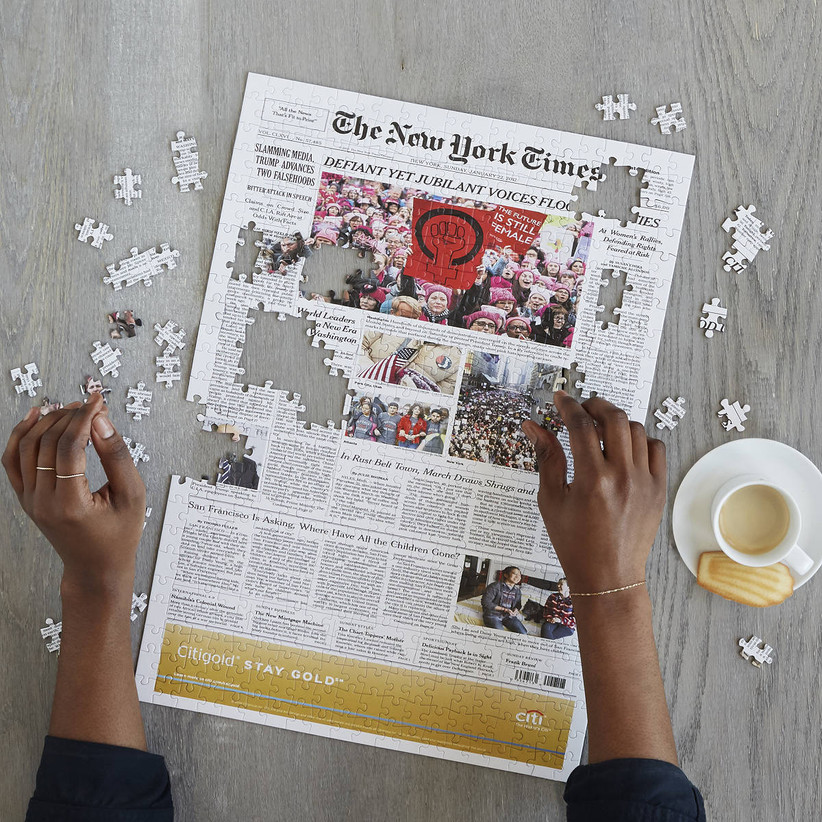 Woman's hands completing custom puzzle of New York Times front page