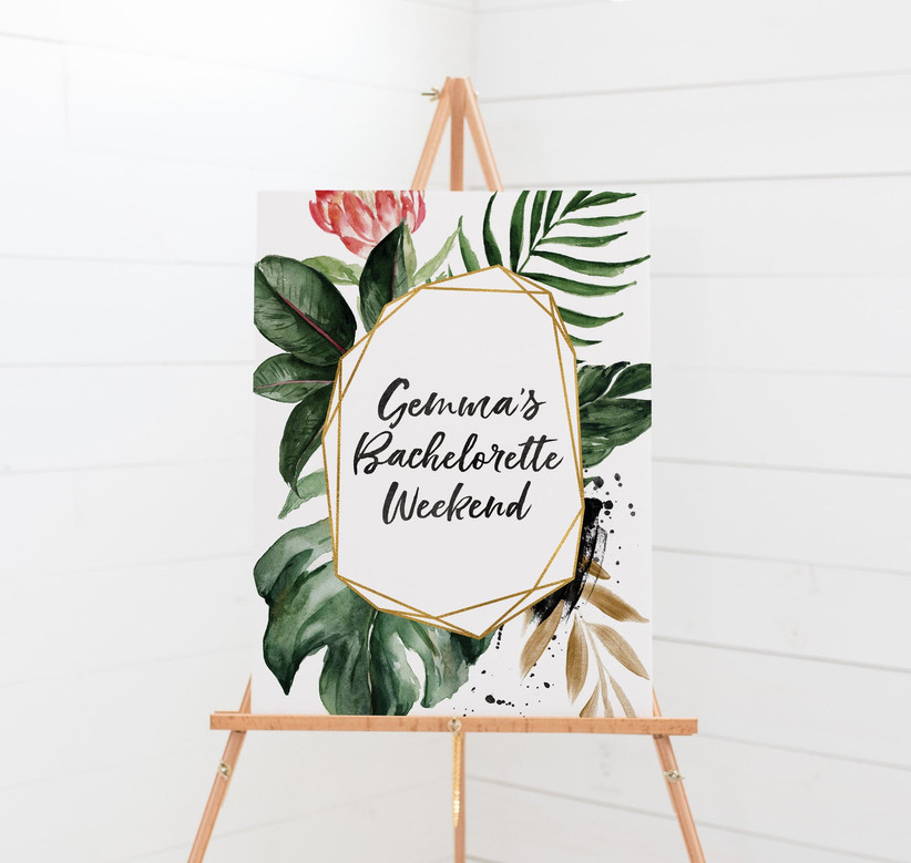 Elegant tropical-theme bachelorette weekend welcome sign on wooden stand