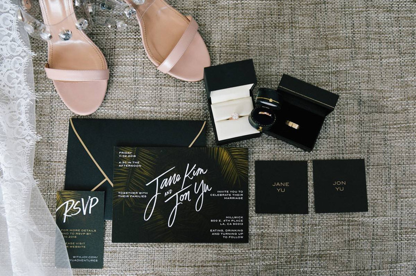 modern black wedding invitations with tropical greenery and white script