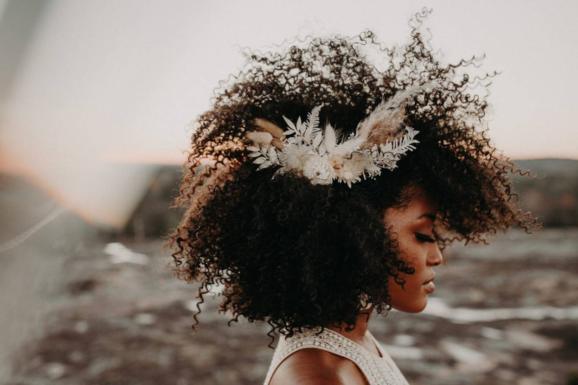 Black bride with natural hair texture wears hair parted to one side and dried greenery and pampas grass hair accessory