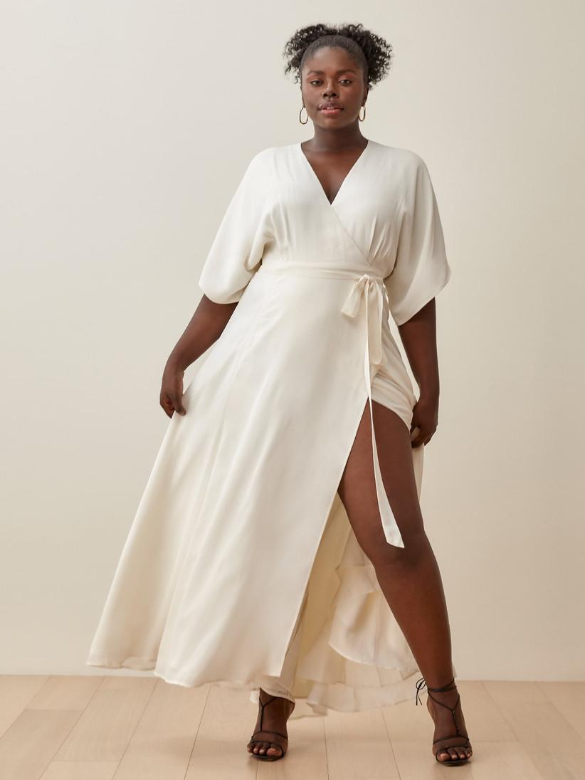 Model wearing minimalist off-white ankle-length wrap wedding dress