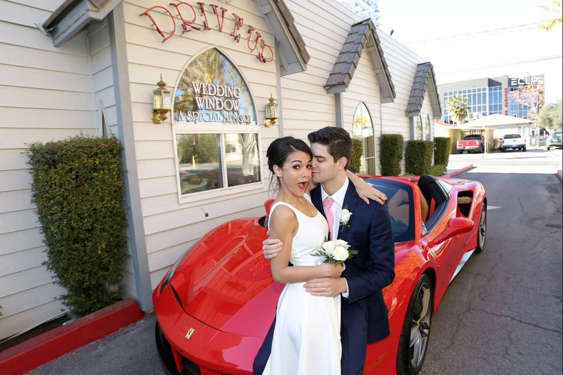 bride and groom lean agains the hood of a red convertible at drive-up las vegas wedding chapel