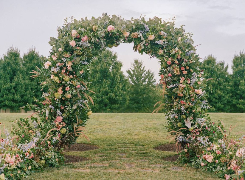 colorful wedding flower arch with greenery, decorative grass, and pink and yellow flowers