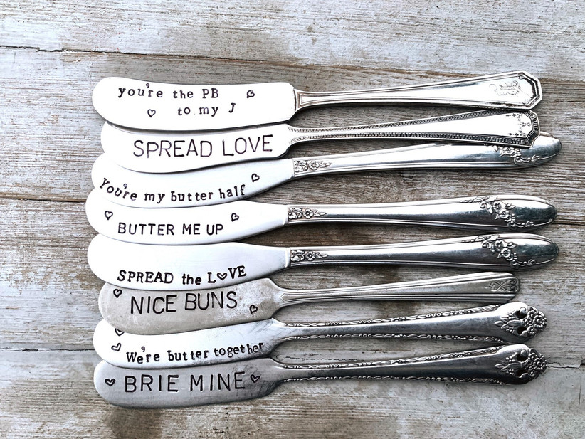 Array of metal spreading knives with cute engravings like Spread the Love
