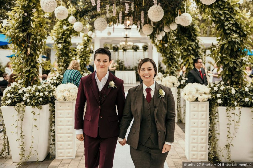 two brides hold hands as they walk down the aisle after exchanging wedding vows. one is wearing a burgundy suit and the other is wearing a brown suit