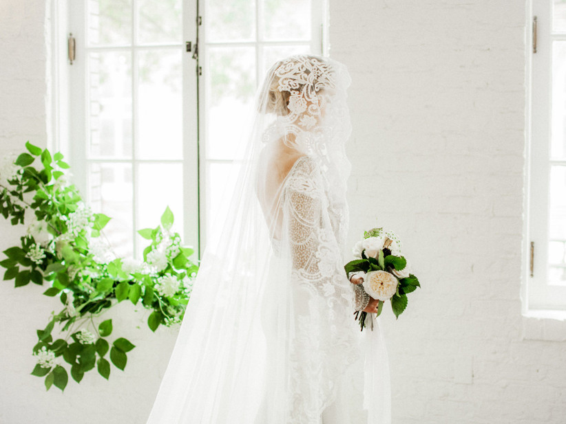 side view of bride wearing lace mantilla veil