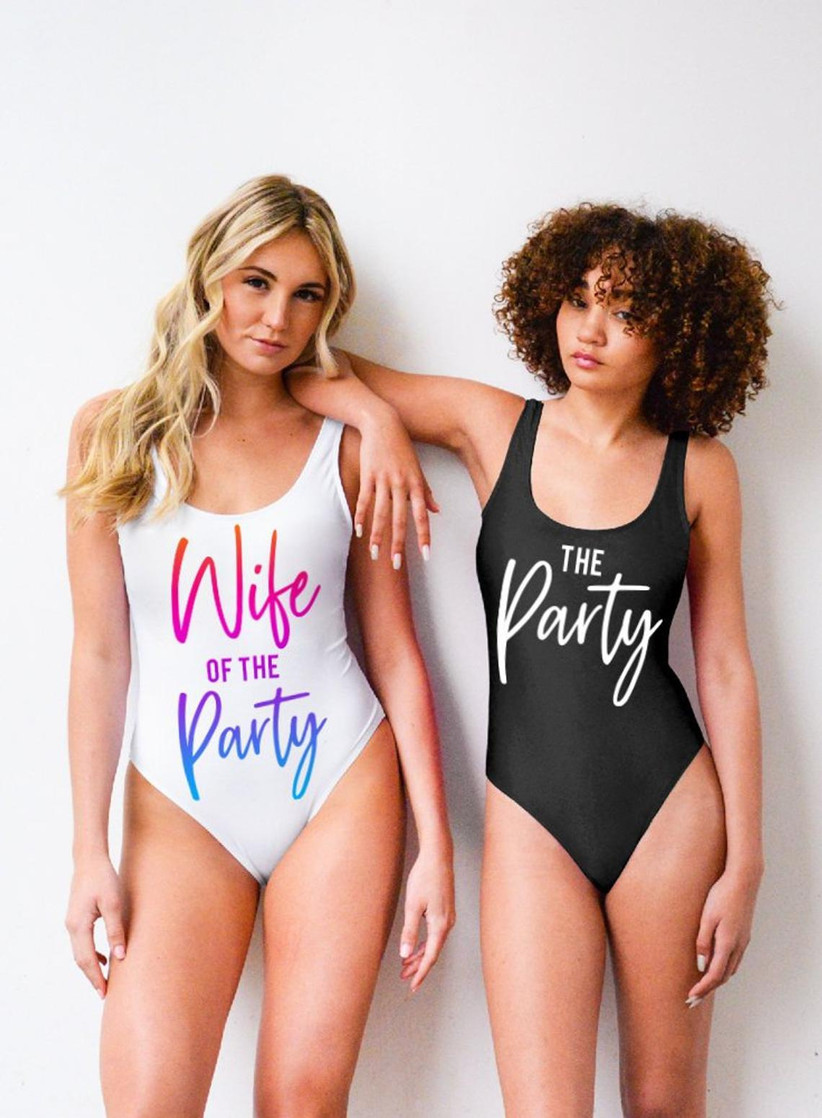 two models stand side by side, one with white swimsuit that says