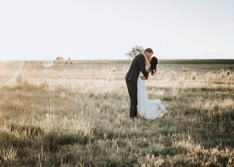 bride and groom kiss in open field