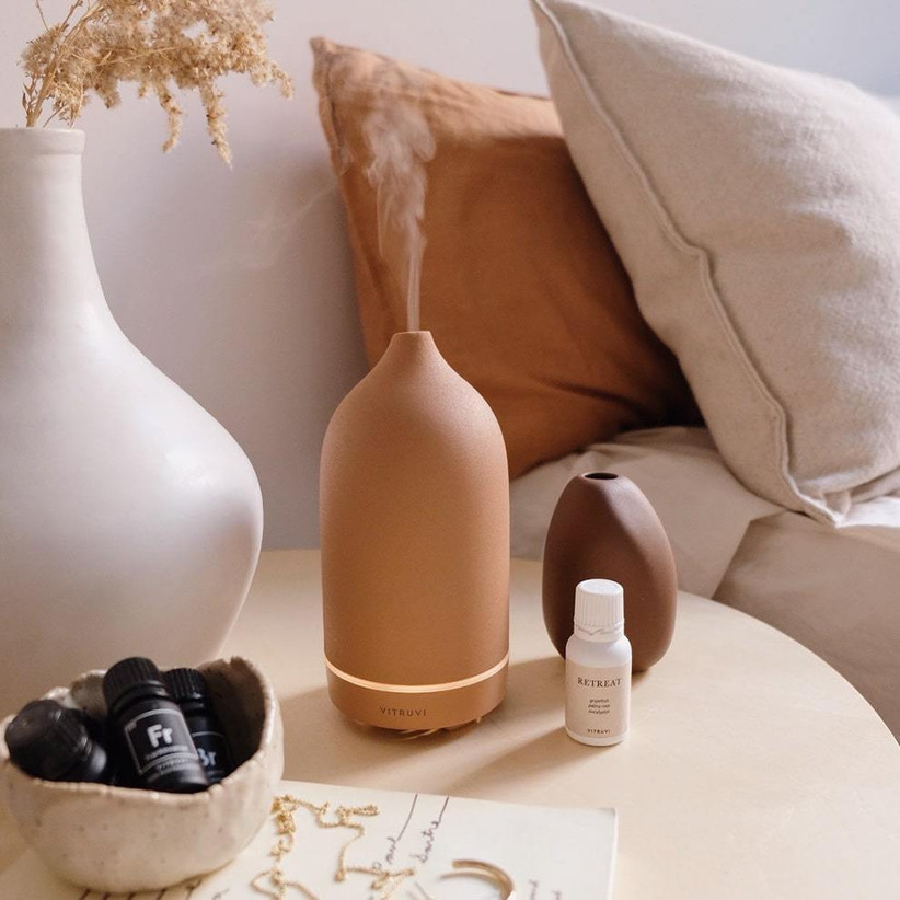 Terracotta-colored porcelain diffuser positioned on bedside table