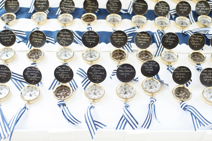 nautical wedding escort card idea gold compasses engraved with guest names