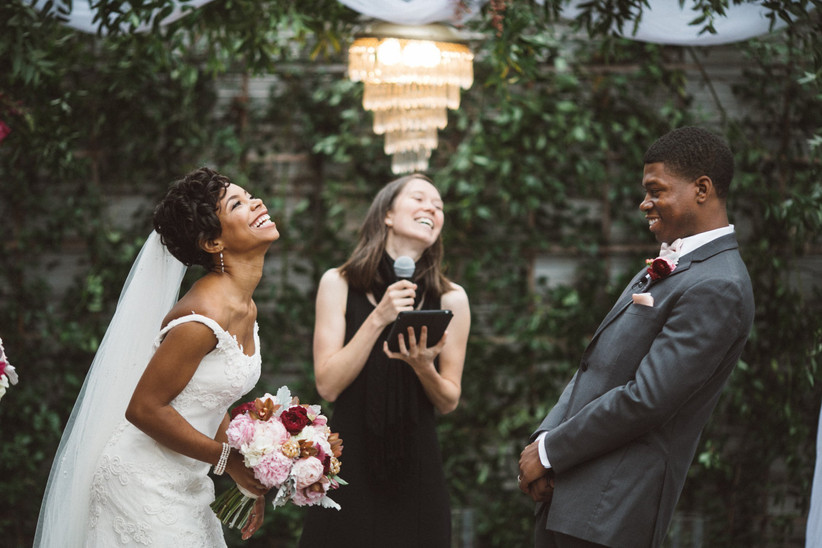 bride and groom stand with their officiant at the altar while laughing