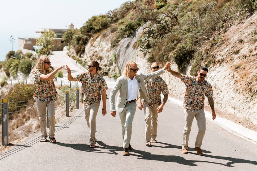groom high-fives groomsman wearing hawaiian button-down shirt as they walk with the rest of the groomsmen