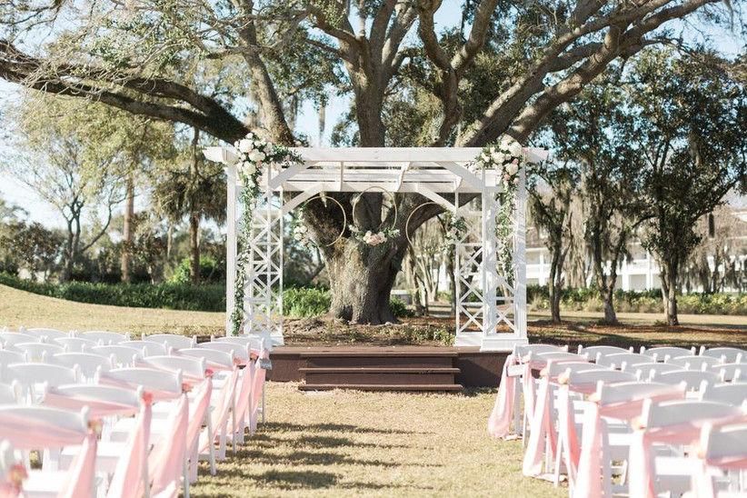 outdoor wedding aisle decor pink sashes tied around chairs along the aisle