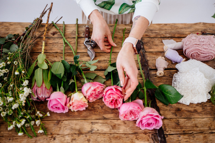 hands trimming pink roses on a table