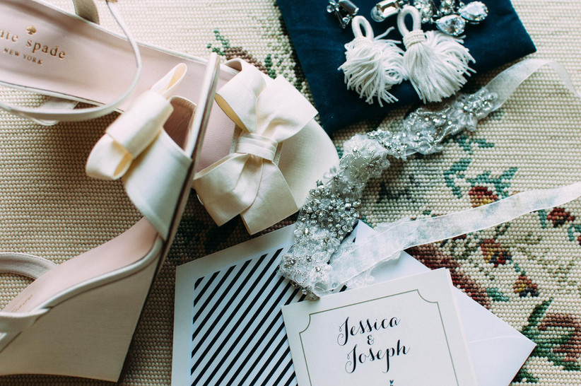 flat lay of black and white wedding paper goods, shoes and accessories