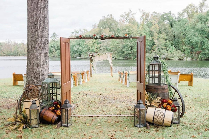 rustic outdoor wedding aisle decor barn doors at the start of the aisle with wagon wheels and barrels for display