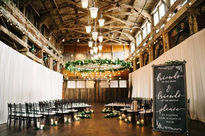indoor wedding ceremony with greenery and edison bulb chandelier