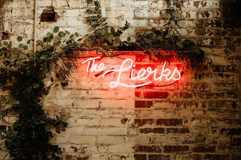 pink neon sign with couple's last name hanging against exposed brick wall with greenery accents