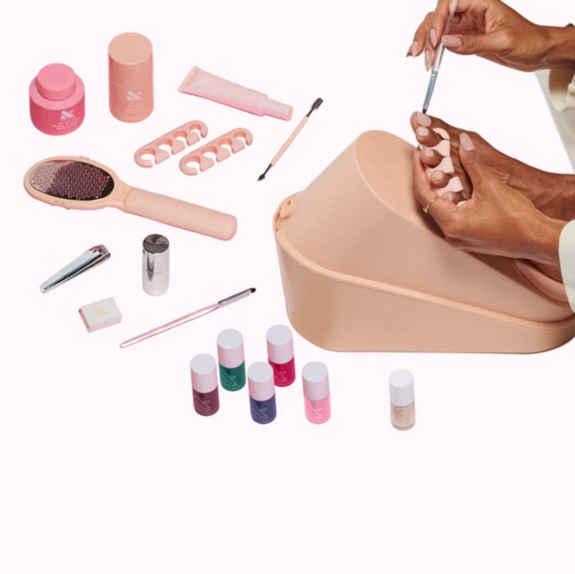 Woman painting toenails with pedicure set around her