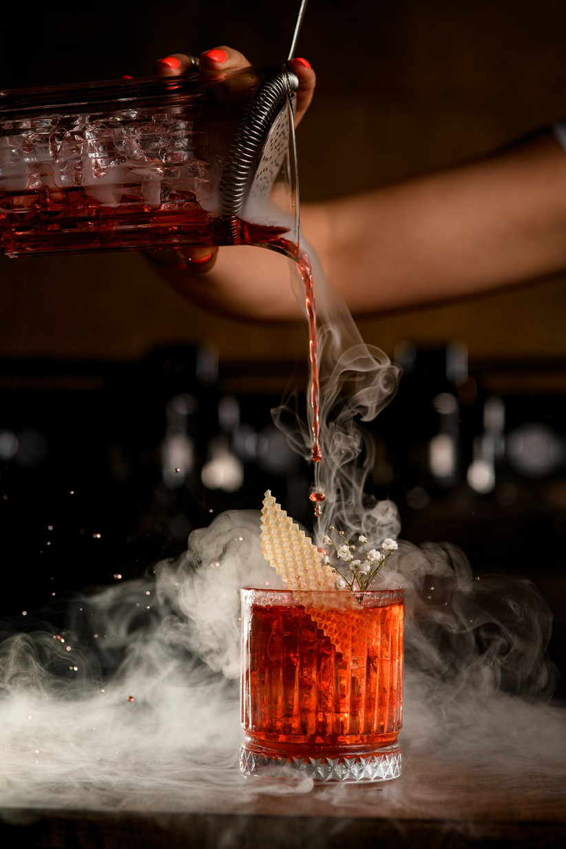 halloween themed wedding idea bartender pours cocktail with dry ice